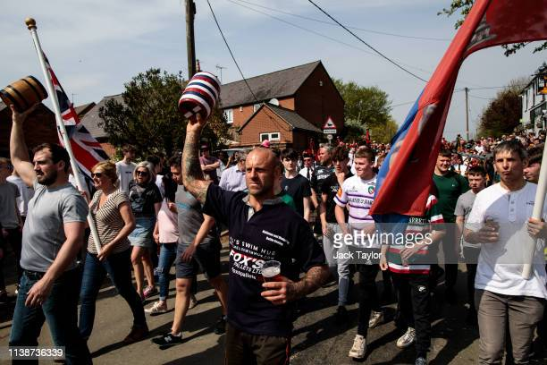 Competitors hold up kegs as they parade through the town ahead of the traditional Easter Monday 'Bottle Kicking' match on April 22 2019 in Hallaton...