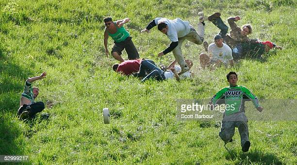 Competitors hurl themselves down a near vertical slope in pursuit of a Double Gloucester cheese during the Gloucestershire 'Cheese Rolling and Wake'...