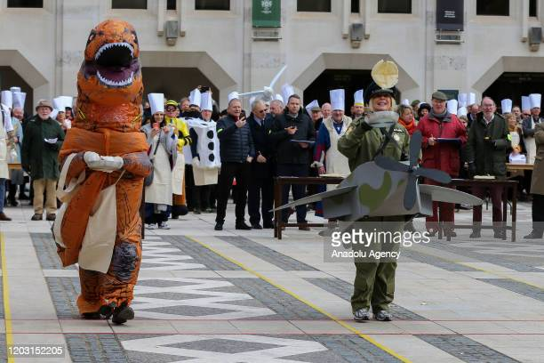 Competitors in fancy dress flips pancakes as they take part in the annual InterLivery Pancake Race on Shrove Tuesday at The Guildhall in London...