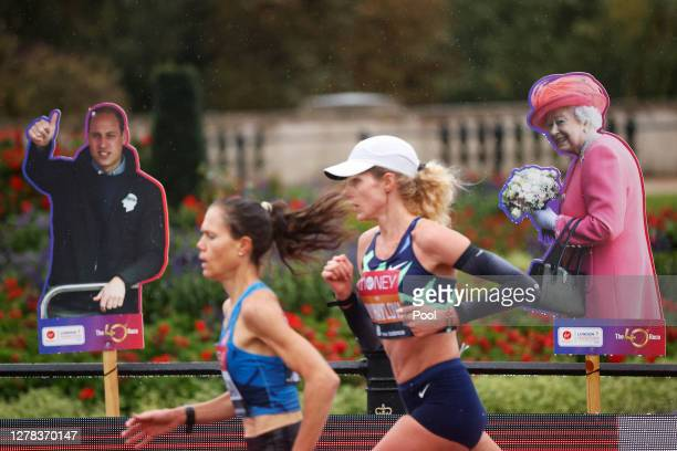 Competitors in the Elite Women's Field run past cardboard cutouts of Prince William Duke of Cambridge and Queen Elizabeth II during the 2020 Virgin...