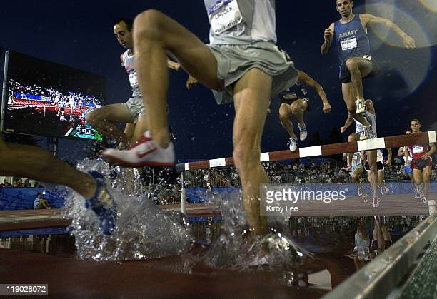 Competitors in the men's steeplechase negotiate the water jump in the U.S. Olympic Track & Field Trials at Sacramento State's Hornet Stadium on...