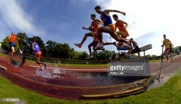 Competitors in the steeplechase negotiate the water jump in the State Junior College Track & Field Championships at American River College in...