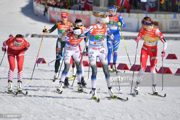 Competitors including Sweden's Frida Karlsson arrive for an exchange during the Ladies' cross country skiing relay 4x5km event at the FIS Nordic...