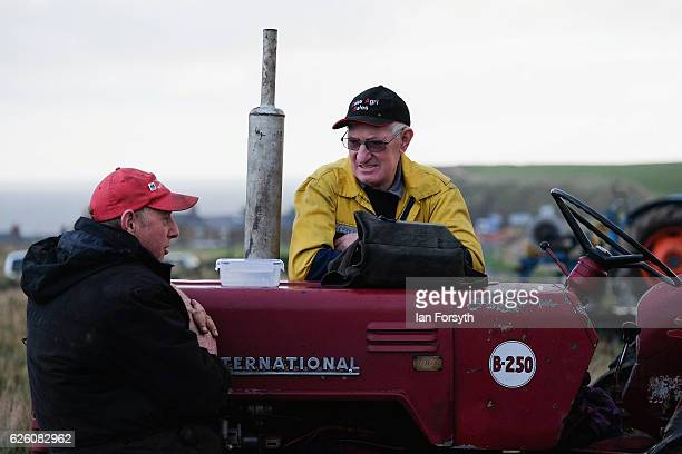 Competitors lean against a tractor and talk during the annual ploughing match on November 27, 2016 in Staithes, United Kingdom. The event which is...