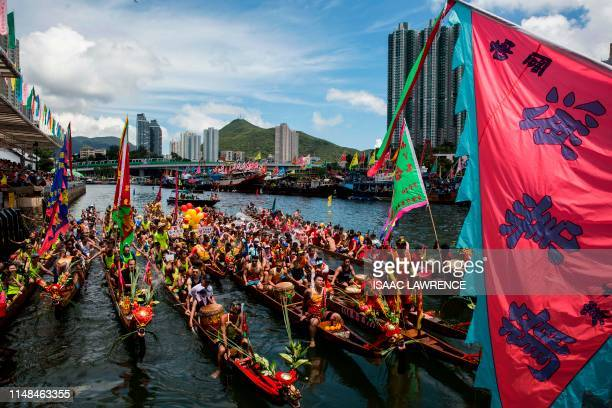 Competitors line up their boats to be presented with flags before splashing each other with water as they take part in the annual dragon boat race...