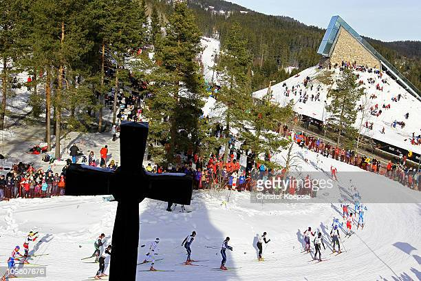 Competitors pass a church along the course in the Men's Cross Country 50km Mass Start race during the FIS Nordic World Ski Championships at...