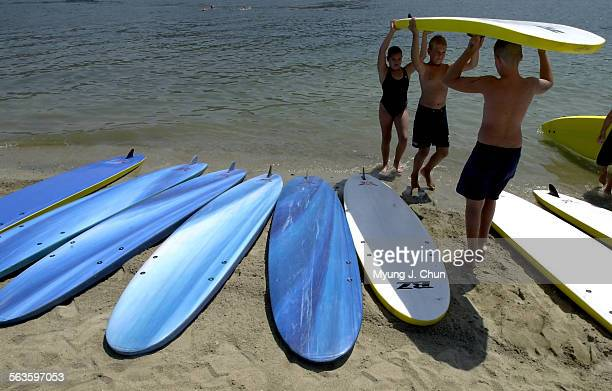 Competitors pick out a paddle board in preparation for the paddle relay of the annual junior lifeguard competition at Castaic Lake Tuesday morning...