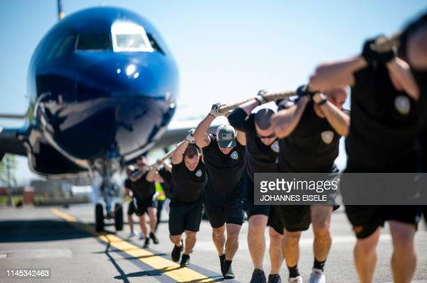TOPSHOT Competitors pull a JetBlue A320 aircraft as they compete in a Plane Pull at John F Kennedy International Airport on May 21 2019 in New York...