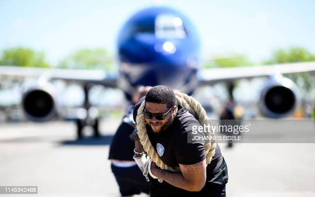 """Competitors pull a JetBlue A320 aircraft as they compete in a """"Plane Pull"""" at John F. Kennedy International Airport on May 21, 2019 in New York. -..."""