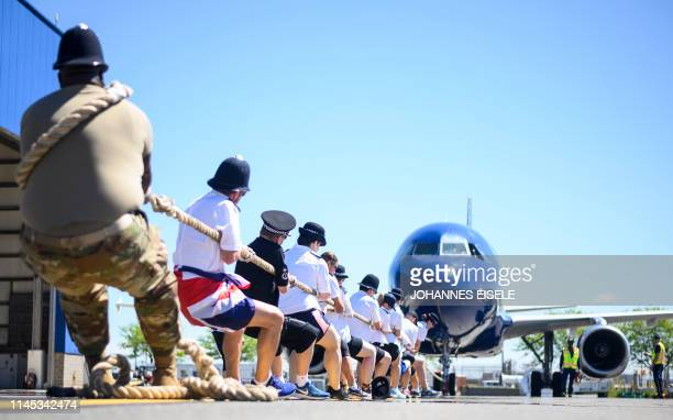 Competitors pull a JetBlue A320 aircraft as they compete in a Plane Pull at John F Kennedy International Airport on May 21 2019 in New York Law...