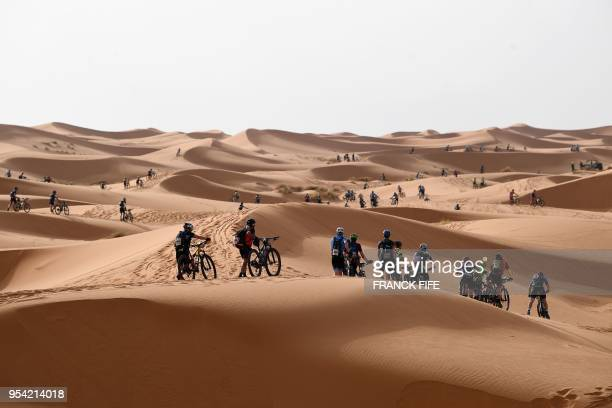 TOPSHOT Competitors push their bikes along a sand dune during Stage 5 of the 13th edition of Titan Desert 2018 mountain biking race around Merzouga...