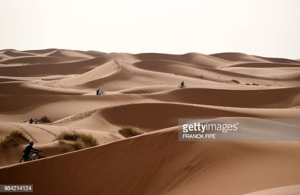 TOPSHOT Competitors push their bikes along a sand dune during Stage 5 of the 13th edition of Titan Desert 2018 mountain biking race around Merzouga...