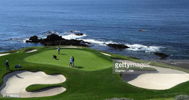 Competitors putt on the seventh green during the final round of the ATT Pebble Beach ProAm the Pebble Beach Golf Links on February 11 2018 in Pebble...