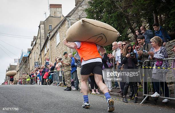 Competitors race carrying woolsacks up the steep Gumstool Hill in the centre of Tetbury on May 25 2015 in Gloucestershire England The race between...
