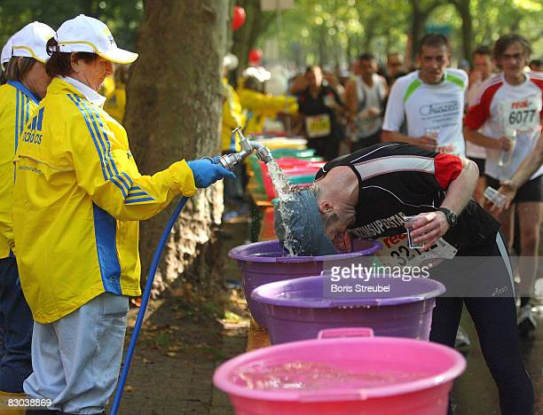 Competitors refresh at a drink stop during the 35th Berlin Marathon on September 28 2008 in Berlin Germany The 35yearold Ethiopian's Haile...