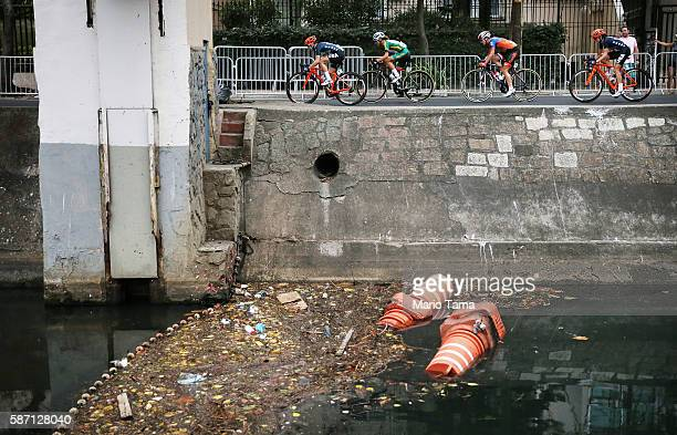 Competitors ride past an 'eco barrier' along a polluted canal in the Leblon neighborhood during the Women's Road Race on Day 2 of the Rio 2016...