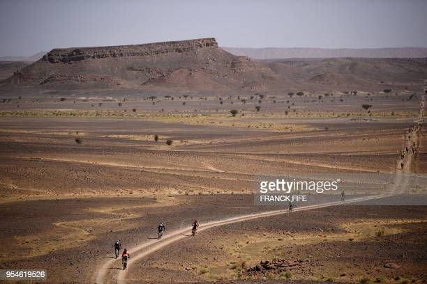 TOPSHOT Competitors ride their bikes during stage 6 of the 13th edition of the Titan Desert 2018 mountain biking race between Merzouga and Maadid on...