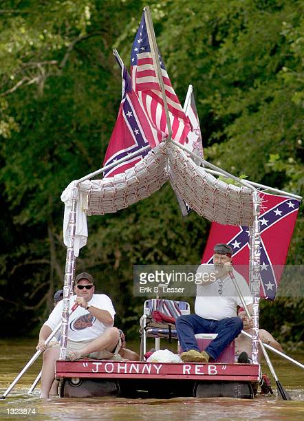 Competitors row a homemade raft covered with more than 300 beer cans during a raft race on the Oconee River as part of the 6th annual Summer Redneck...