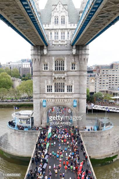 Competitors run across Tower Bridge as they compete in the 2019 London Marathon in central London on April 28 2019 / Restricted to editorial use...