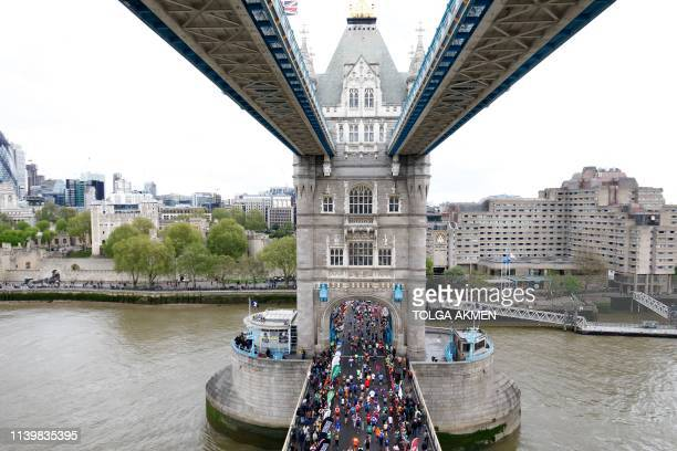 TOPSHOT Competitors run across Tower Bridge as they compete in the 2019 London Marathon in central London on April 28 2019 / Restricted to editorial...
