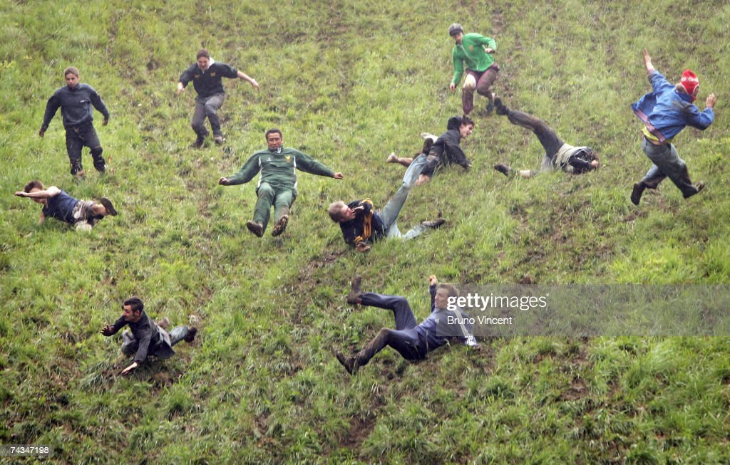 Competitors run and fall down Coopers Hill during the Cheese rolling event on May 28, 2007 in Brockworth, England. The annual tradition which is thought to date back to Roman times draws competitors from far and wide to chase the cheese 200 yards down a near vertical slope in pursuit of a seven-pound Double Gloucester cheese. Injuries are commonplace, even forcing the cancellation of the event in the past.