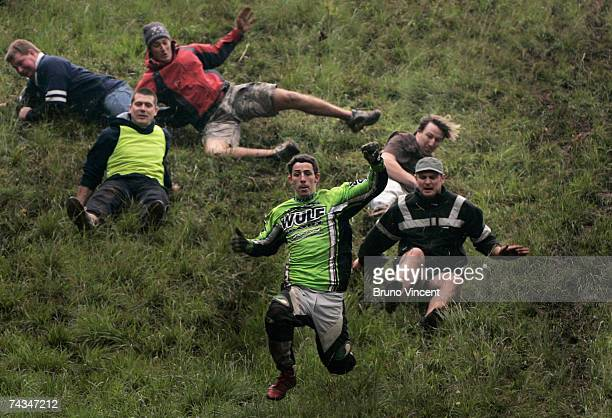 Competitors run and fall down Coopers Hill during the Cheese rolling event on May 28 2007 in Brockworth England The annual tradition which is thought...