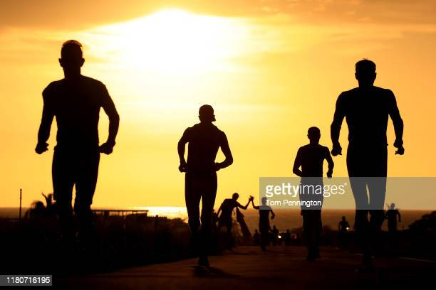 Competitors run as the sun sets during the Ironman World Championships on October 12 2019 in Kailua Kona Hawaii