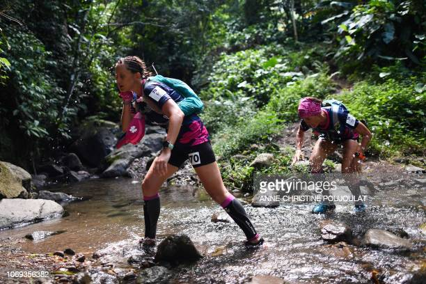 Competitors run as they take part in the trail race of the Raid des Alizes an exclusively allfemale multi sport competition on the French Caribbean...