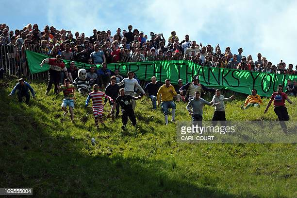 Competitors run down Coopers Hill in pursuit of a fake foam round Double Gloucester cheese during the annual cheese rolling and wake near the village...