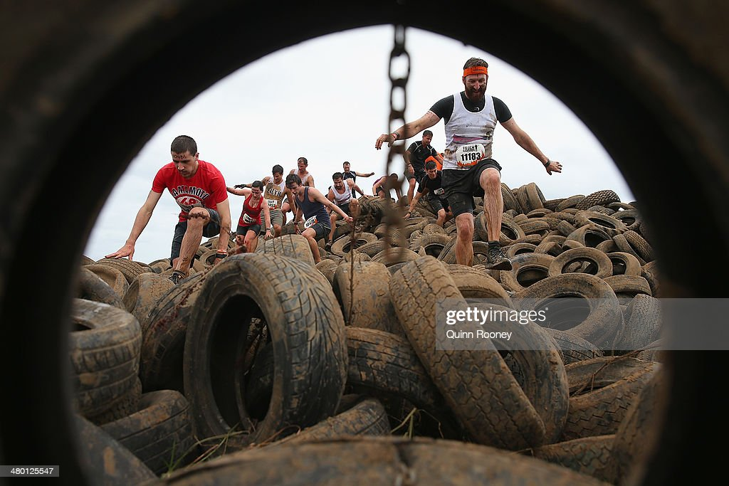 Competitors run over a tyre pit during Toughmudder at