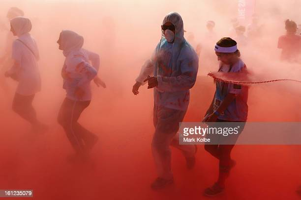 Competitors run through the pink colour throw area during the Colour Run at Sydney Olympic Park on February 10 2013 in Sydney Australia