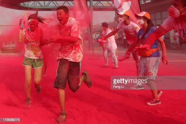 Competitors run through the red colour throw area during the Colour Run at the Beijing International Garden Expo park on August 10 2013 in Beijing...