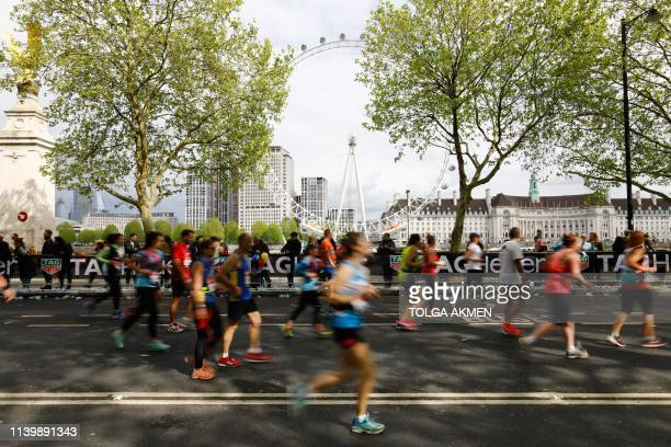 Competitors run with along The Embankment with the London Eye seen in the background as they compete in the 2019 London Marathon in central London on...