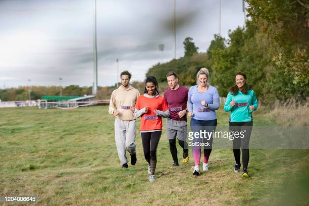 competitors running together at outdoor charity event - competition group stock pictures, royalty-free photos & images