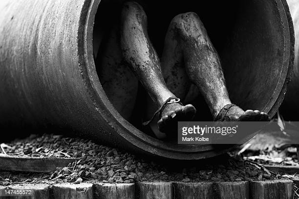 A competitors shoes are seen as he crawls through a concrete pipe in the Plumber's Crack obstacle as he competes in the Tough Bloke Challenge at the...