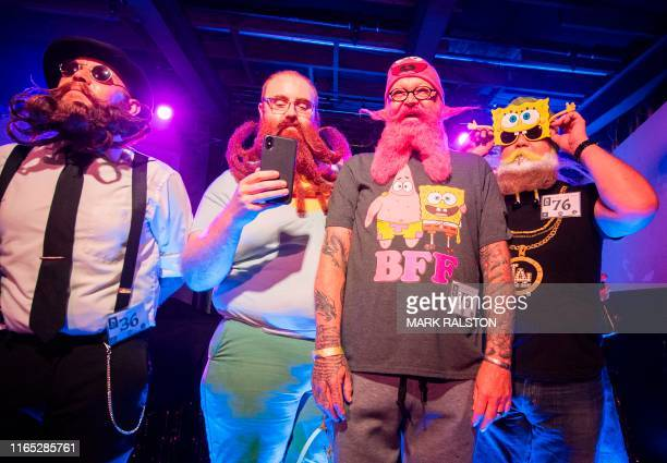 Competitors stand on stage in the annual Beard and Mustache Battle to raise money for charity at the Resident Bar in Los Angeles California on August...