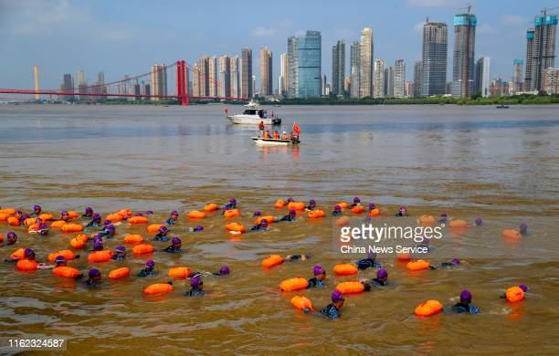 Competitors swim across the Yangtze River during the 45th Wuhan International Yangtze River Crossing Festival on July 16 2019 in Wuhan Hubei Province...