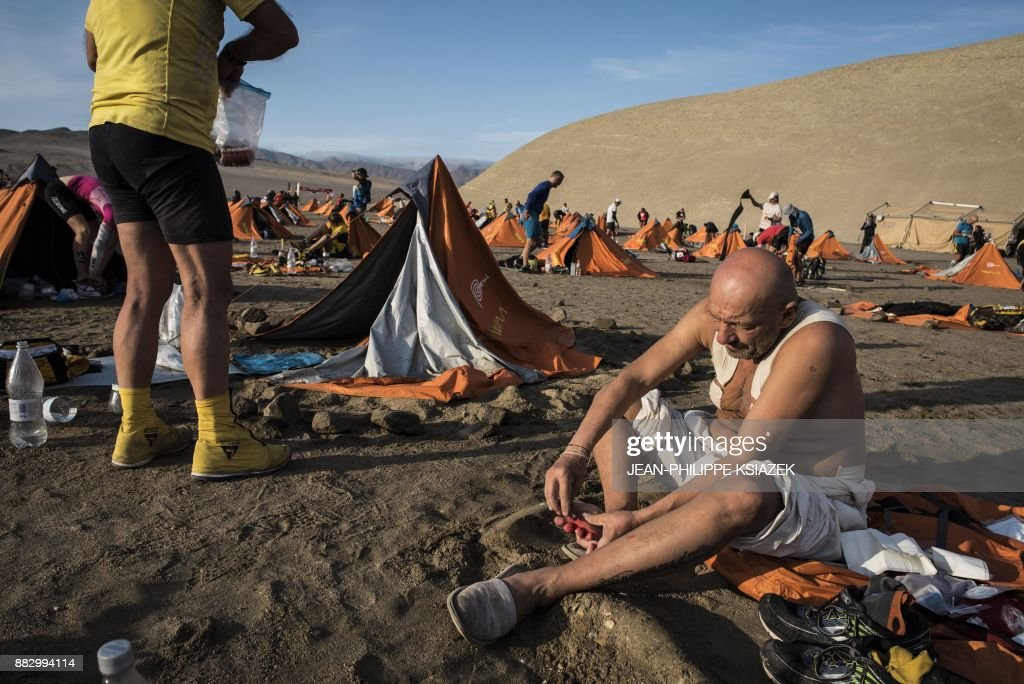TOPSHOT - Competitors take a break during the third stage of the first edition of the Marathon des Sables Peru, between Samaca and Ocucaje, in the Ica desert, on November 30, 2017. Competitors compete in the race of approximately 250 kms, which is divided into six stages through the Ica Desert at a free pace and in self-sufficiency conditions from November 28 to December 4, 2017. /