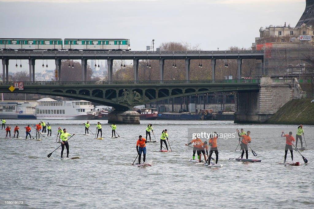 Competitors take part in a stand up paddle race on the Seine river in Paris as a train of the Paris metro runs on the Bir-Hakeim bridge, on December 9, 2012. This event is part of the 52nd Paris International Boat Show (Salon nautique).