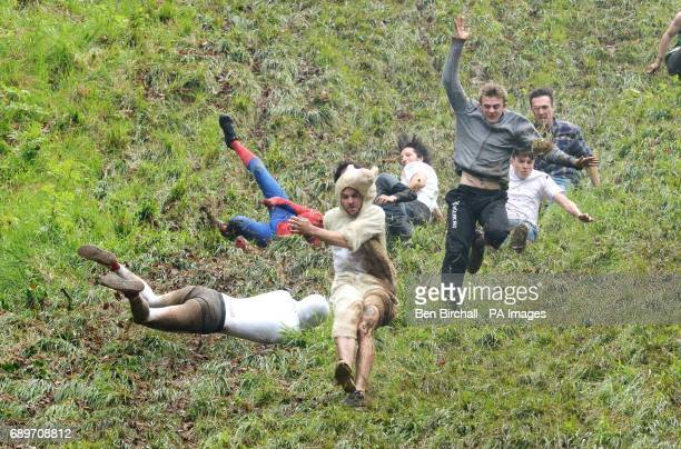 Competitors take part in the annual unofficial cheese rolling at Cooper's Hill in Brockworth Gloucestershire where a cheese has been chased down the...