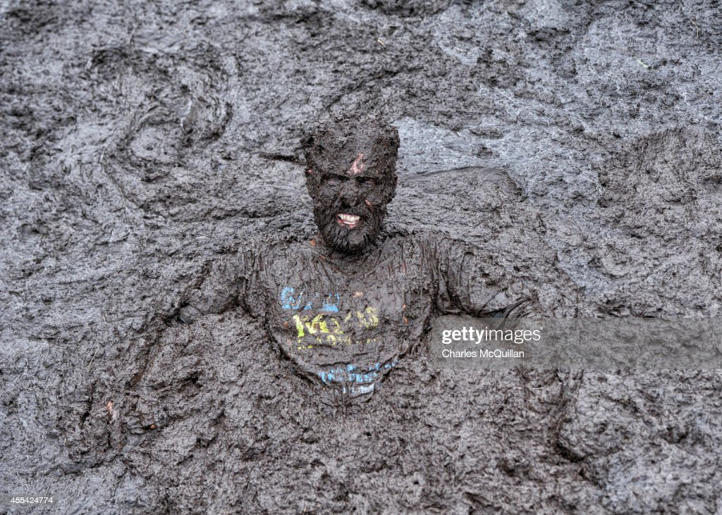 Competitors take part in the McVitties Mud Madness race at Foymore Lodge on September 14, 2014 in Portadown, Northern Ireland. The four mile run takes place through a mucky course of fields, ponds and bogs and sees over a thousand runners make their way over obstacles including a tyre pit, foxhole and sink holes in aid of the Marie Curie Cancer Care charity. (Photo by Charles McQuillan/Getty Images).