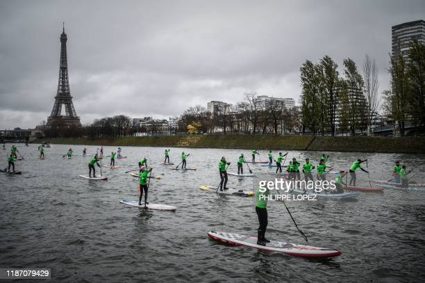 Competitors take part in the Nautic Paddle Race on the Seine river near the Eiffel tower in Paris on December 8 2019 About 1000 competitors took part...