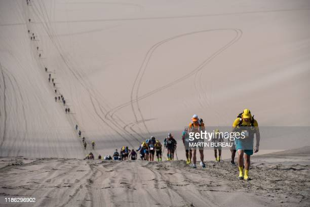 Competitors take part in the second stage of the 2nd Half Marathon Des Sables Ica DesertPeru in Paracas Peru on December 3 2019 Competitors compete...
