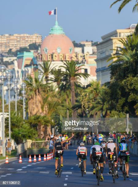Competitors take the start of the bicycle race after completing the swimming race of the 13th Ironman thriathlon in Nice on July 23 with the Negresco...