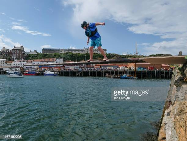 A competitors takes part in the greasy pole competition in Whitby Harbour during the annual Whitby Regatta on August 10 2019 in Whitby England At...