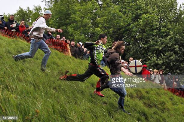 Competitors throw themselves down Coopers Hill in pursuit of a round Double Gloucester cheese on May 26 2008 during the annual cheese rolling and...