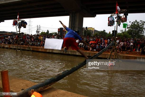 Competitors try to cross the greased areca nut pool above Kalimalang river to win the prizes while participating in the areca nut climbing...