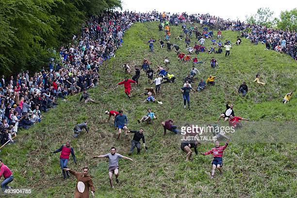 Competitors tumble down Coopers Hill in pursuit of a round Double Gloucester cheese during the annual cheese rolling and wake near the village of...