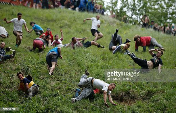 TOPSHOT Competitors tumble down Coopers Hill in pursuit of a round Double Gloucester cheese during an annual cheese rolling competition near the...