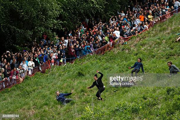 Competitors tumble down Cooper's Hill in pursuit of a round Double Gloucester cheese during the annual Cooper's Hill cheese rolling competition near...